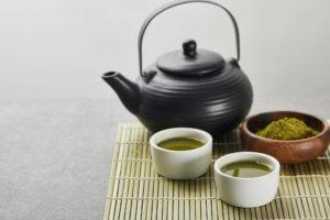 schwarze Teekanne mit Matcha-Pulver auf Bambusmatte